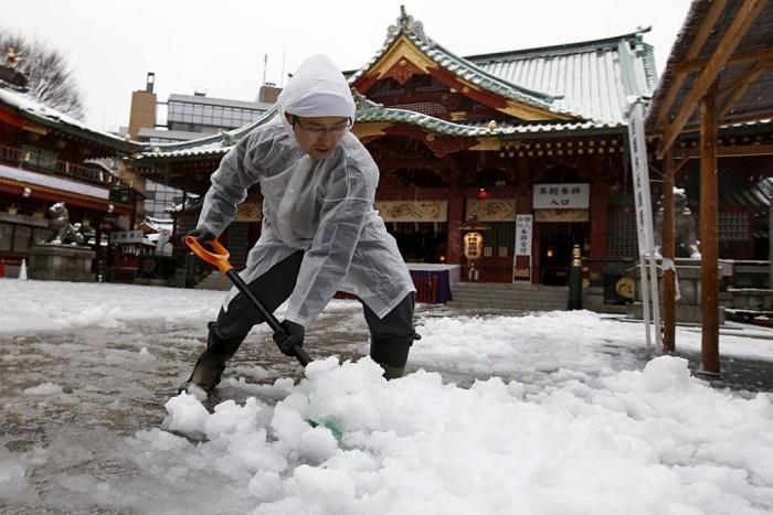 Мигрант из Китая убирает снег перед рестораном в Нью-Йорке
