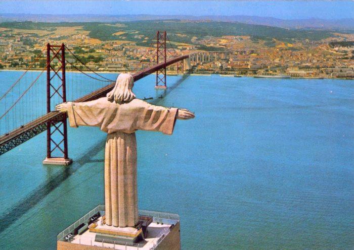 Статуя Христа Спасителя в Алмаде на фоне моста через реку Тежу