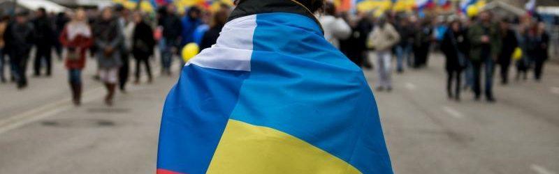 Человек с флагами России и Украины на плечах