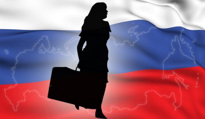 Переселенец на фоне российского флага