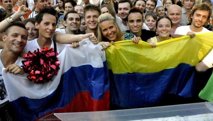 Российский и украинский флаги в руках молодежи