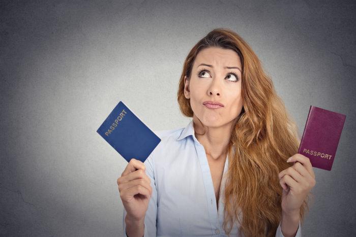 Девушка держит в руках паспорта разных стран