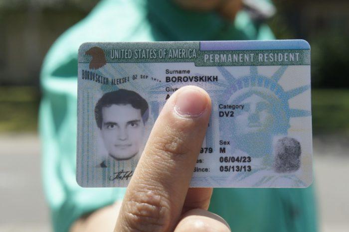 Человек держит Green Card