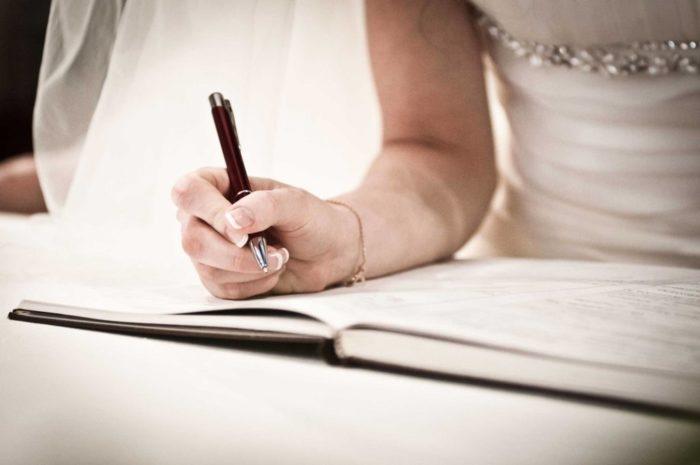 Невеста ставит подпись в загсе