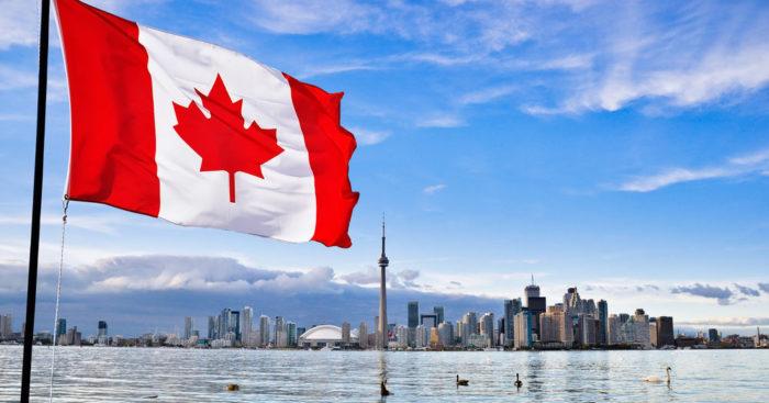 Флаг Канады на фоне города на побережье