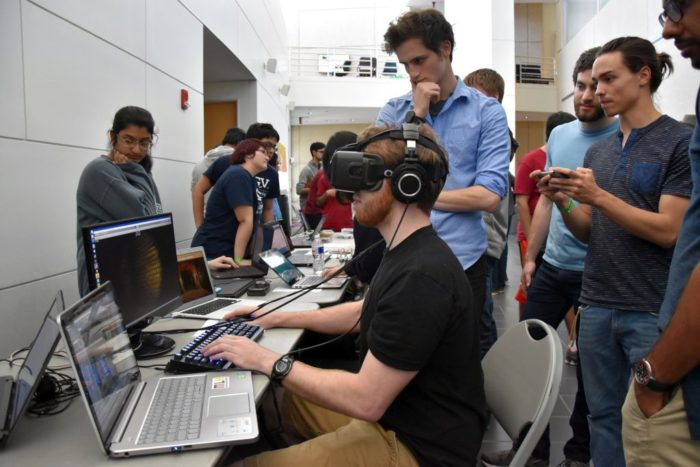Молодые люди в комнате, один из которых сидит за компьютером в очках виртуальной реальности и наушниках