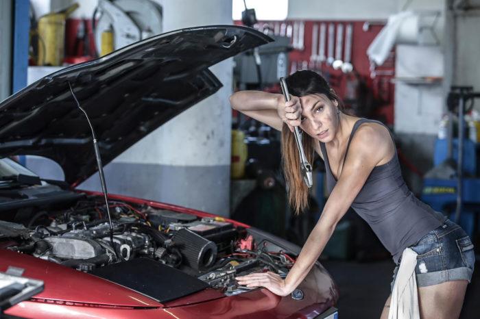 Девушка чинит автомобиль
