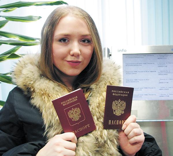 Студентка держит в руках загранпаспорт