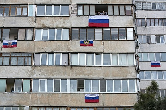 Жители многоэтажки вывешивают флаги РФ на балконы