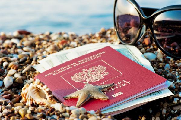 Загранпаспорт на морских камнях и солнечные очки