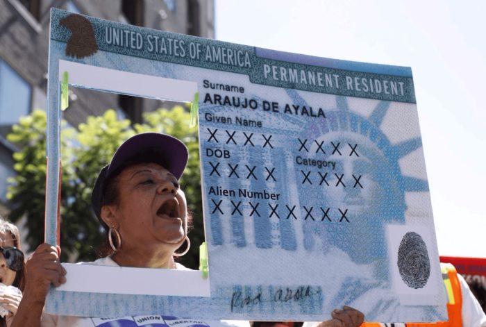 Женщина с картонной имитацией Зелёной карты на митинге