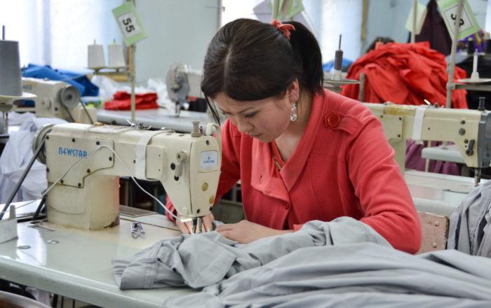 Женщина за работой в швейном цехе
