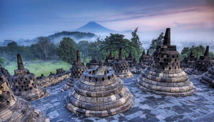 Буддийские ступы в Индонезии на фоне вулкана