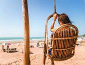 Девушка в подвесном кресле на пляже