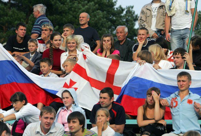 Люди с флагами России и Грузии