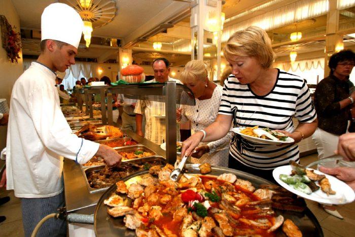 Посетители отеля выбирают еду на шведском столе