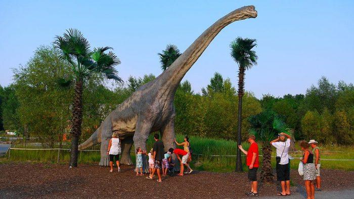 Туристы около модели динозавра в Динопарке