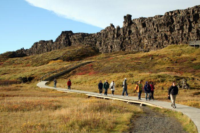 Туристы идут по деревянному помосту в парке Тингвеллир на фоне горных образований