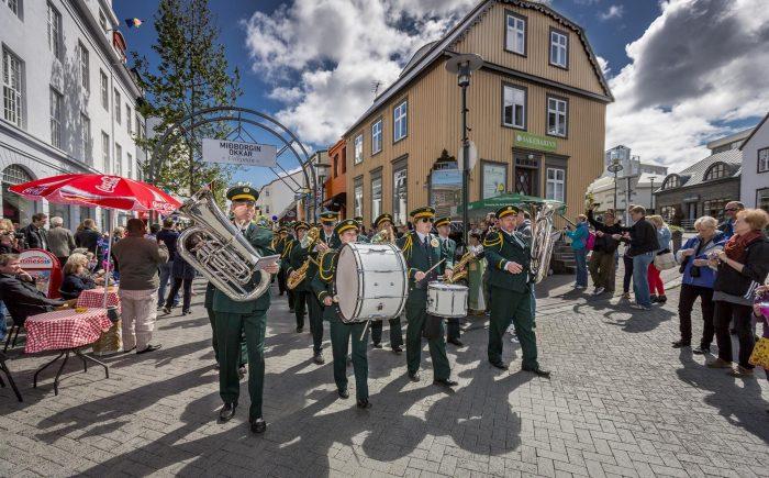 Марширующий оркестр идёт по улице на празднике в Рейкьявике