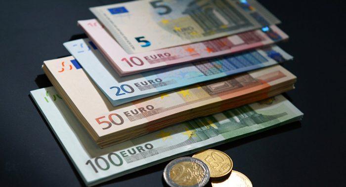 Купюры евро разного номинала и монеты евро на чёрном полотне