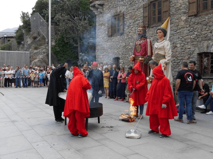 Жители Андорры в красных карнавальных костюмах на праздновании Фестиваля огня