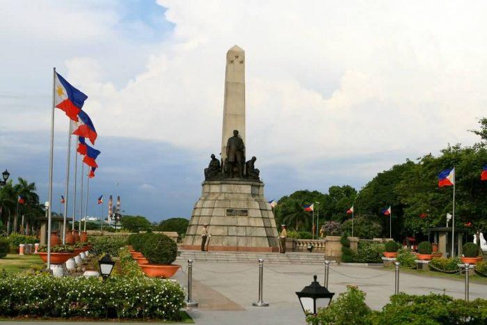 Монумент Хосе Рисаля на фоне флагов в Парке Рисаль, Манила