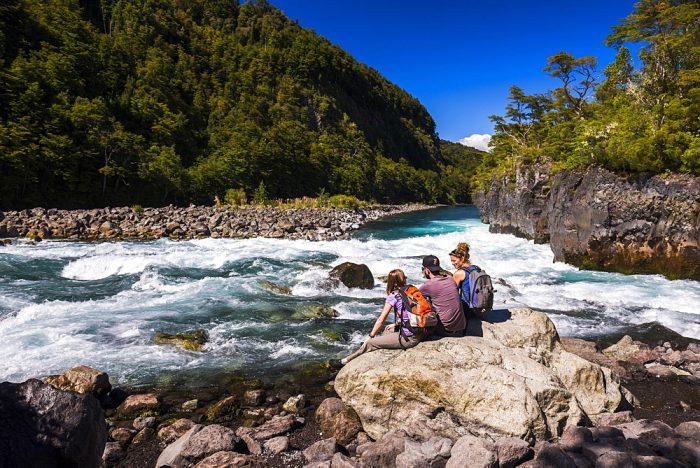 Люди сидят на камнях на берегу реки