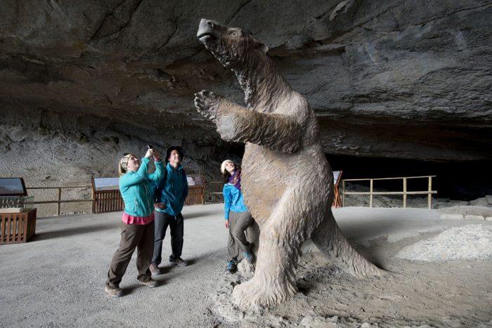 Молодые люди фотографируют фигуру древнего животного