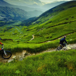Велосипедисты едут по тропе среди лугов Муранской планины